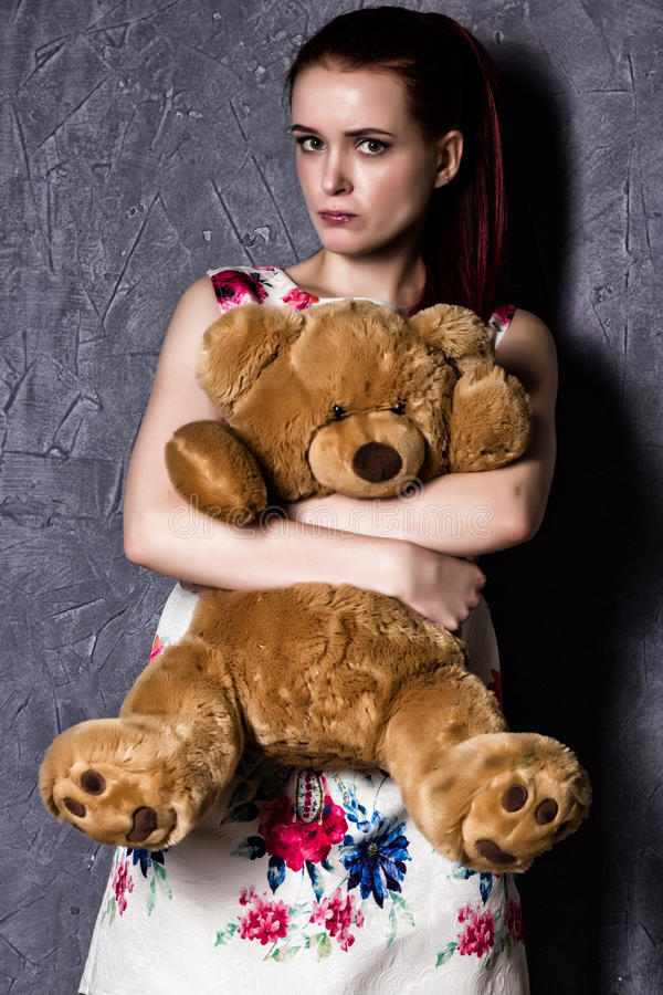 Bella la donna pensierosa o offensiva abbraccia un orsacchiotto riguarda un fondo grigio fotografia stock libera da diritti
