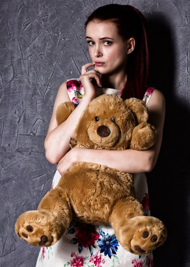 Bella la donna pensierosa o offensiva abbraccia un orsacchiotto riguarda un fondo grigio immagine stock