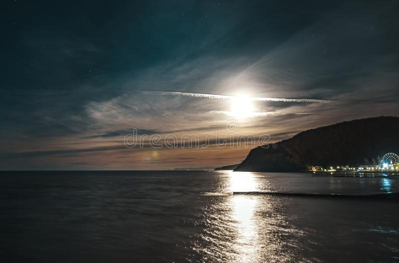 Bella luna piena sopra la montagna ed il mare fotografia stock