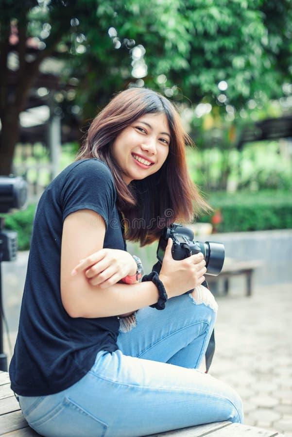 Bella macchina fotografica asiatica della tenuta della donna nel giardino fotografie stock