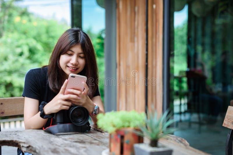 Bella macchina fotografica asiatica della tenuta della donna nel giardino immagini stock libere da diritti