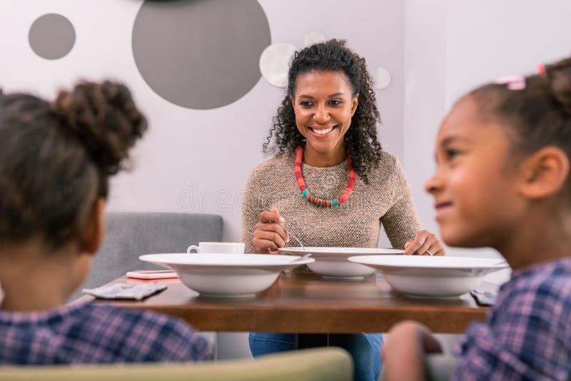 Bella madre alla moda che ritiene pranzare estremamente felice con i suoi bambini immagini stock libere da diritti