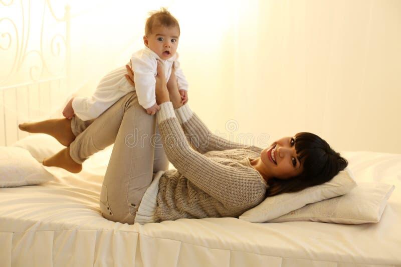Bella madre con brevi capelli scuri ed il suo piccolo neonato sveglio immagine stock