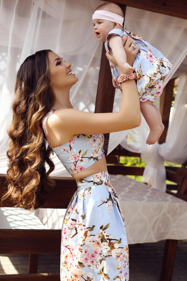 Bella madre con capelli scuri lunghi che posano con il suo piccolo bambino sveglio in simili vestiti immagine stock