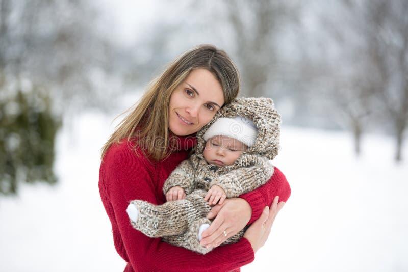Bella madre e neonato sveglio nel onesie tricottato, avendo Tak immagine stock