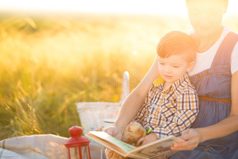 Bella madre e suo il figlio sveglio che leggono un libro su un picnic sui precedenti di tramonto Concetto felice di istruzione e  fotografia stock libera da diritti