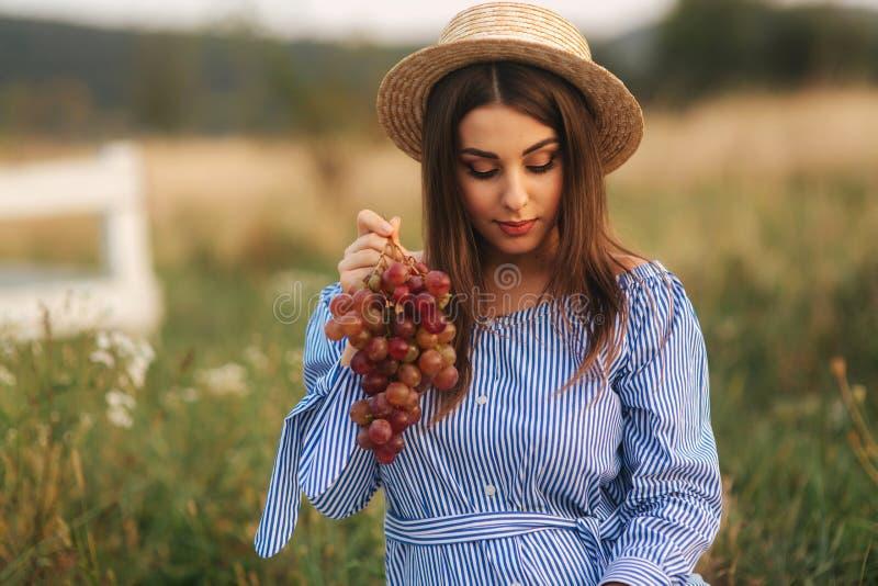 Bella manifestazione della donna incinta e mangiare l'uva rossa Alimento sano Frutta fresca Sorriso felice della donna fotografia stock libera da diritti