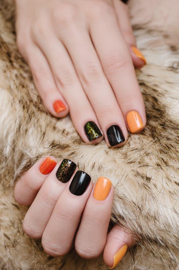 Bella mano femminile con arte arancio e nera del chiodo immagini stock libere da diritti