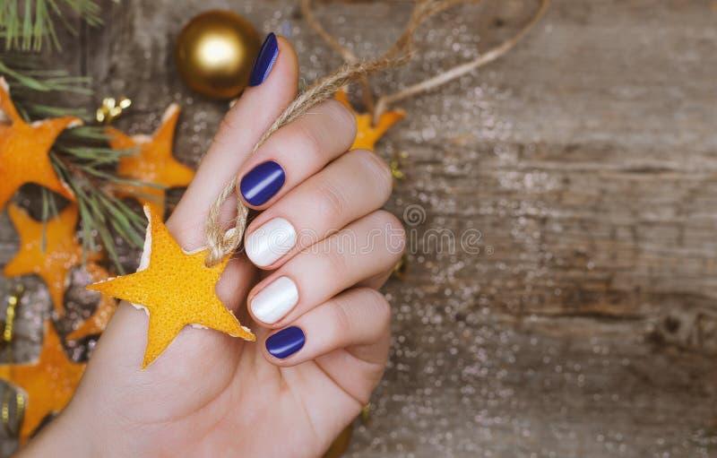 Bella mano femminile con progettazione rossa e bianca del chiodo Manicure di Natale fotografia stock