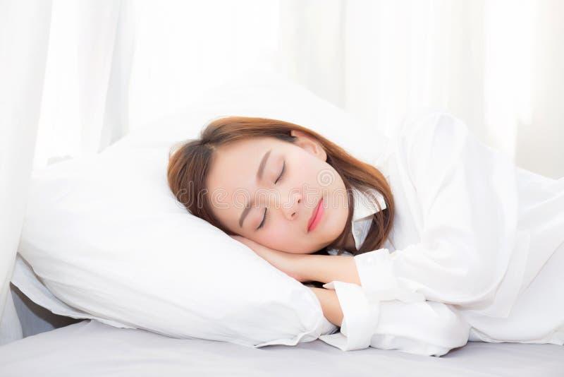 Bella menzogne asiatica di sonno della giovane donna a letto sulla camera da letto con la testa sul cuscino comodo e felice fotografia stock