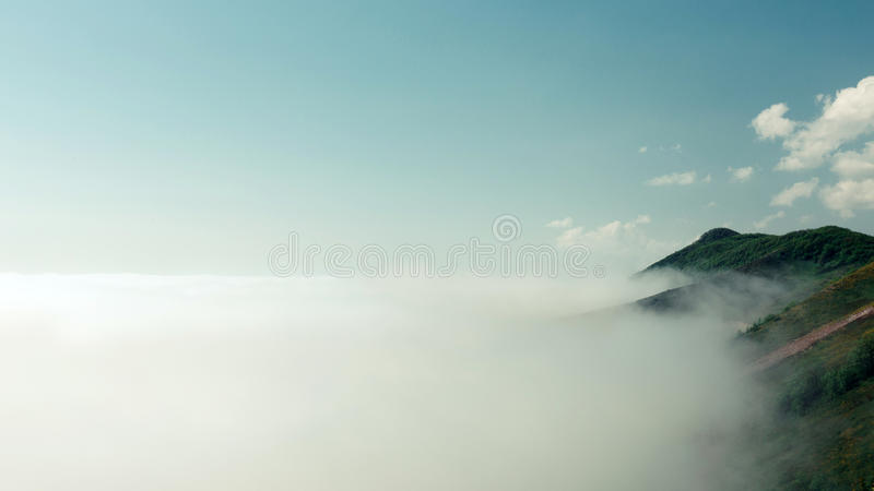 Bella natura del paesaggio nella mattina sulla montagna di punta con la nebbia della nuvola di luce solare ed il cielo blu lumino fotografia stock