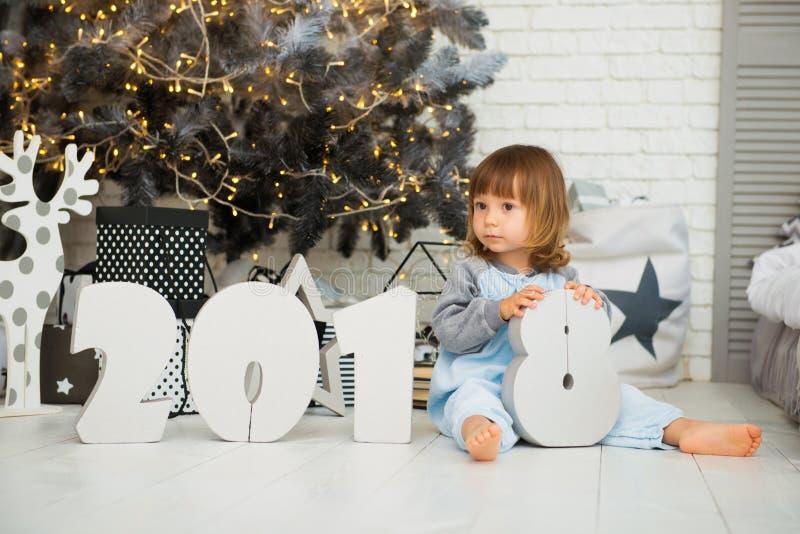 Bella neonata emozionale con figure 2018 che sorride vicino all'albero di Natale immagine stock
