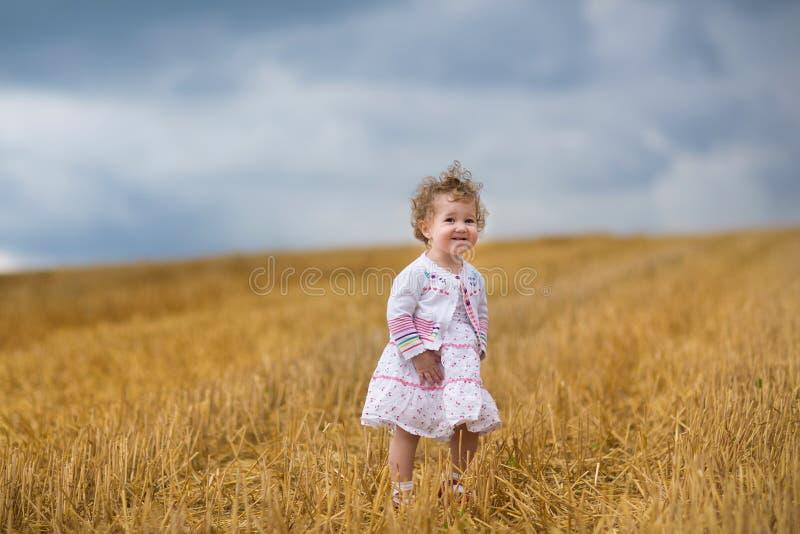 Bella neonata riccia che cammina in un giacimento di grano dorato immagine stock libera da diritti