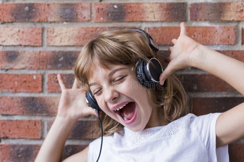 bella niñita con auriculares en casa escuchando música y canto, tecnología y concepto musical. Fondo de ladrillo imagen de archivo libre de regalías
