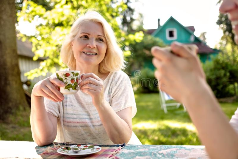 Bella nonna bionda che si rilassa con la sua famiglia al giardino immagini stock
