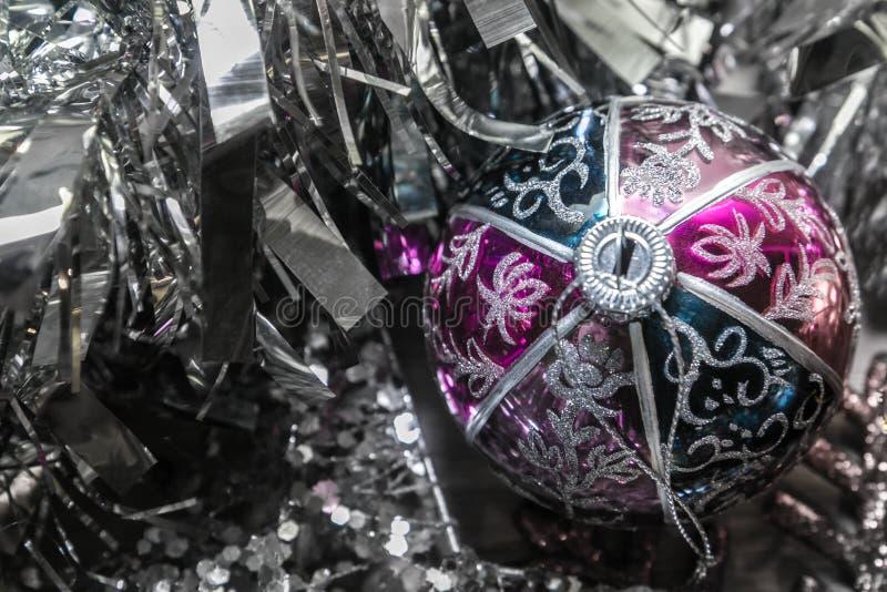 Bella palla di natale circondata dalle decorazioni d'argento brillanti immagine stock libera da diritti