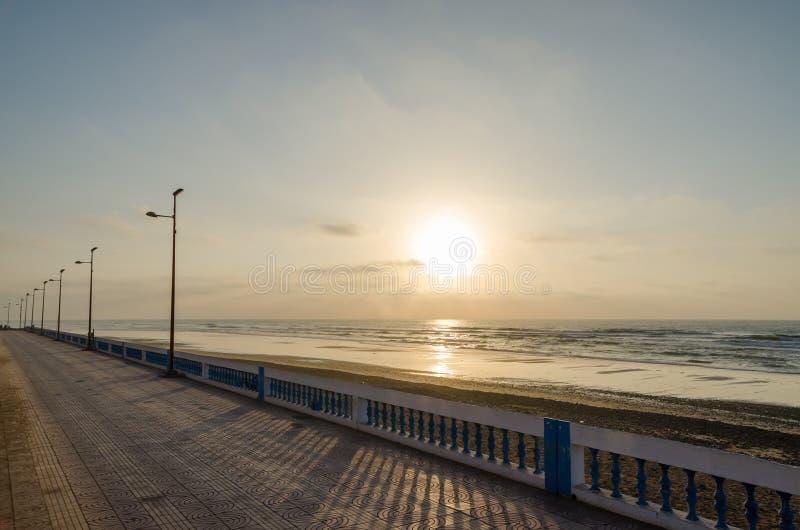 Bella passeggiata atlantica della spiaggia con il passaggio pedonale di pietra durante il tramonto a Sidi Ifni, Marocco, Nord Afr fotografia stock libera da diritti