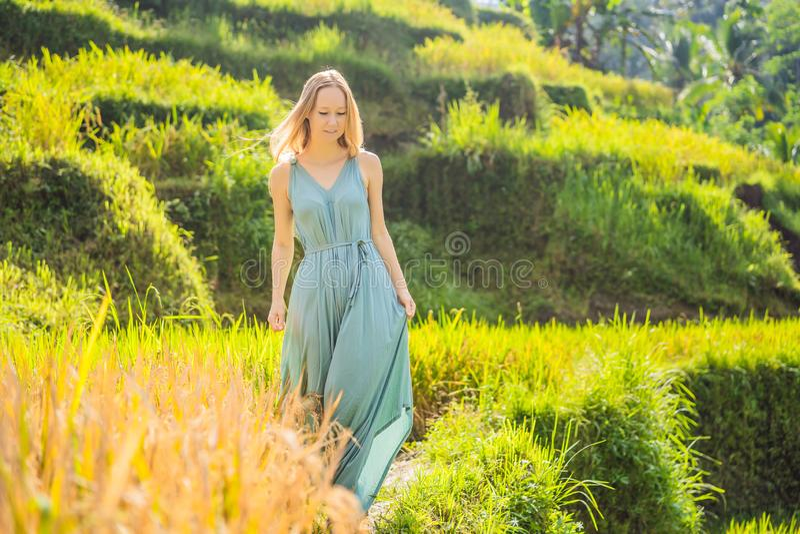 Bella passeggiata della giovane donna al pendio di collina asiatico tipico con riso che coltiva, terrazzi del giacimento del riso fotografia stock libera da diritti