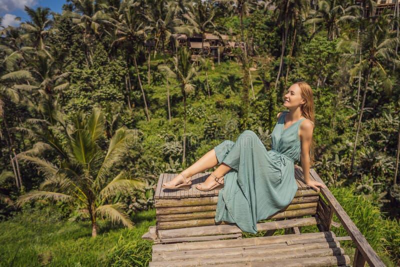 Bella passeggiata della giovane donna al pendio di collina asiatico tipico con riso che coltiva, terrazzi del giacimento del riso fotografia stock