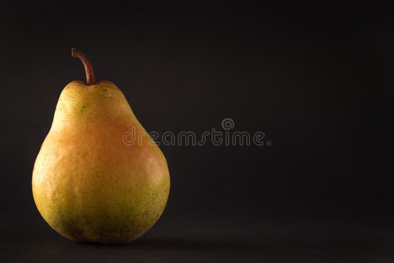 Bella pera gialla matura su fondo nero immagini stock libere da diritti