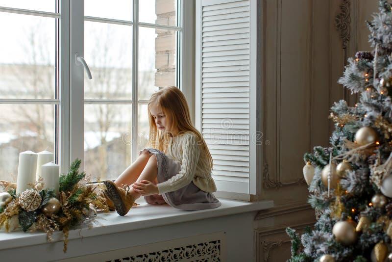 Bella piccola ragazza bionda con gli occhi azzurri che si siedono sulla finestra immagine stock libera da diritti