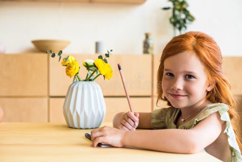 bella piccola ragazza della testarossa che assorbe taccuino e sorridere fotografie stock libere da diritti