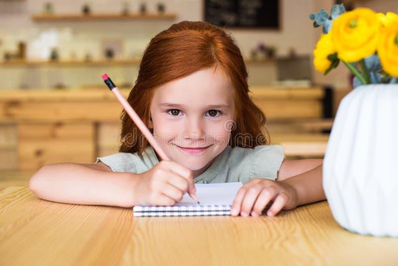 bella piccola ragazza della testarossa che assorbe taccuino e sorridere fotografia stock