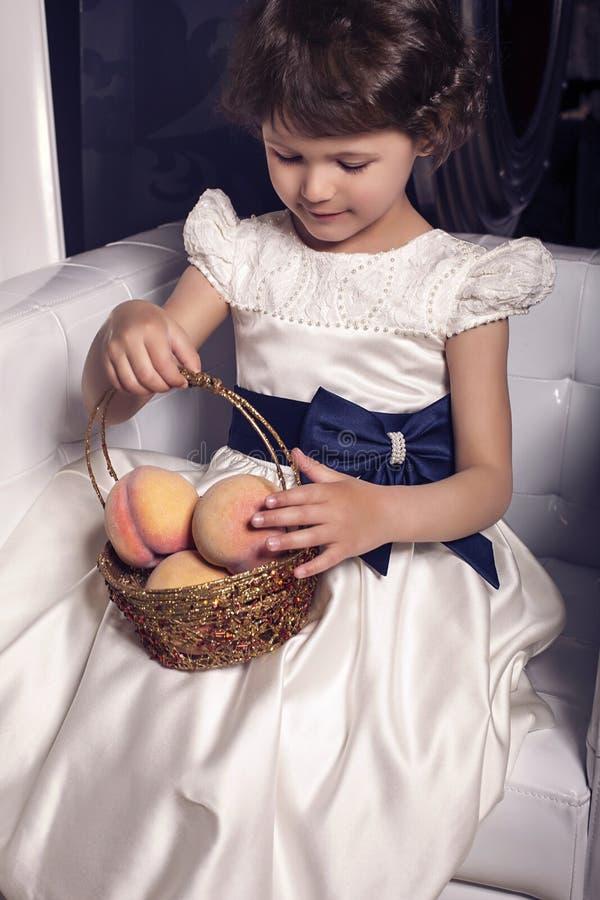 Bella piccola ragazza sveglia con la frutta delle pesche fotografia stock libera da diritti