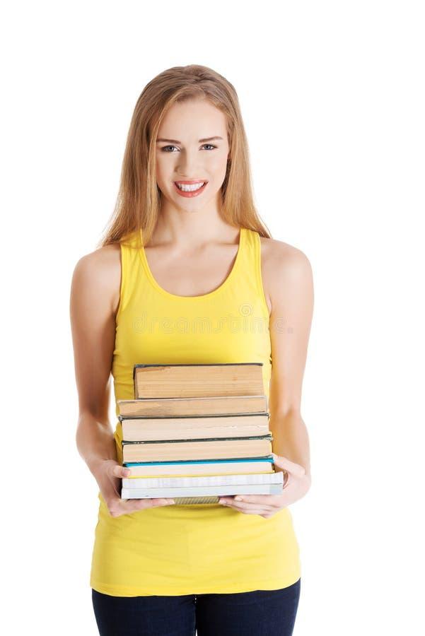 Bella pila caucasica casuale della tenuta della studentessa di libri. fotografia stock libera da diritti