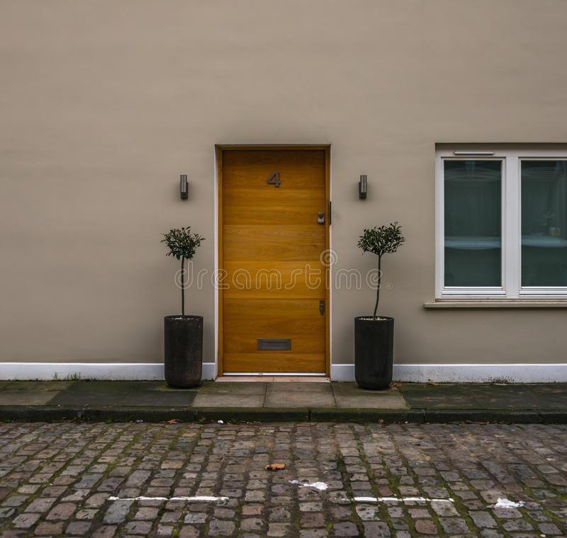 Bella porta di legno alla casa beige, bello legno naturale sulla b fotografia stock