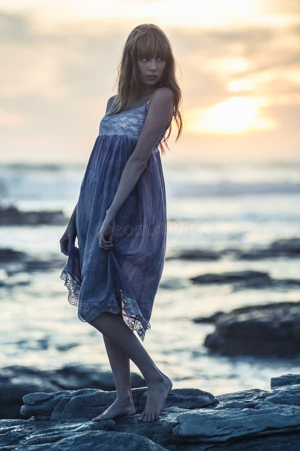 Bella posa di modello sulle rocce dal mare fotografia stock