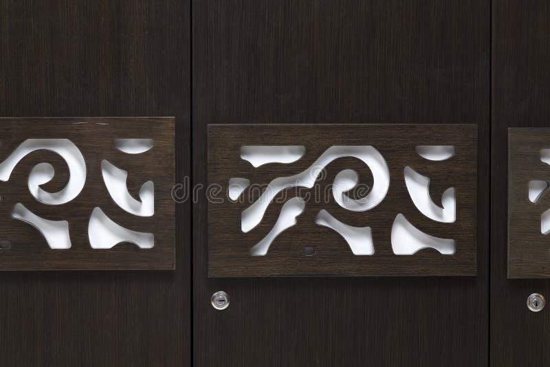 Bella progettazione di sguardo moderna contemporanea su una porta del guardaroba fatta di compensato marrone scuro fotografia stock libera da diritti