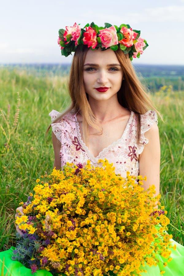 Bella ragazza abbastanza splendida alla moda in vestito sul giacimento di fiori Ragazza piacevole con la corona dei fiori lei cap immagine stock