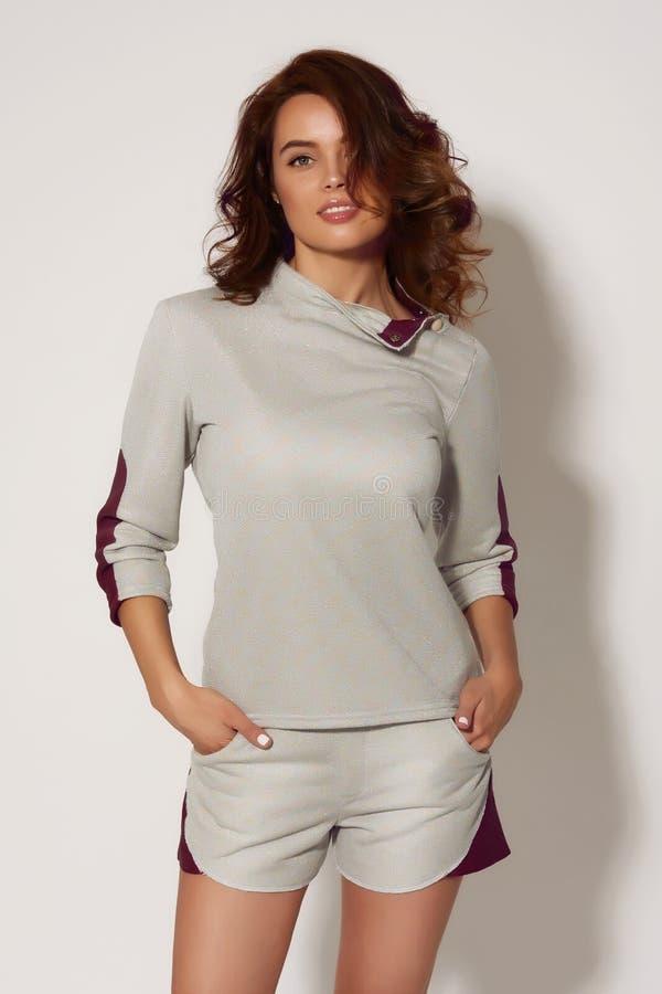 Bella ragazza abbronzata sexy con capelli ricci scuri in vestiti comodi casuali per la camminata e gli sport, in una blusa beige  fotografie stock libere da diritti