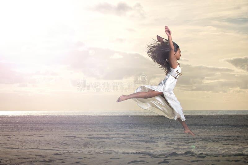 Bella ragazza africana che salta in vestito bianco fotografia stock libera da diritti