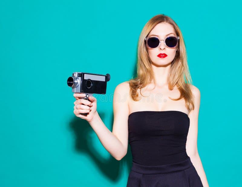 Bella ragazza alla moda che posa e che tiene una cinepresa d'annata in vestito ed occhiali da sole neri sui precedenti verdi in fotografia stock