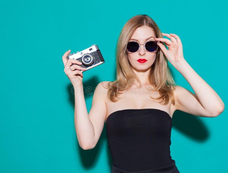 Bella ragazza alla moda che posa e che tiene una macchina fotografica d'annata in vestito ed occhiali da sole neri sui precedenti immagini stock