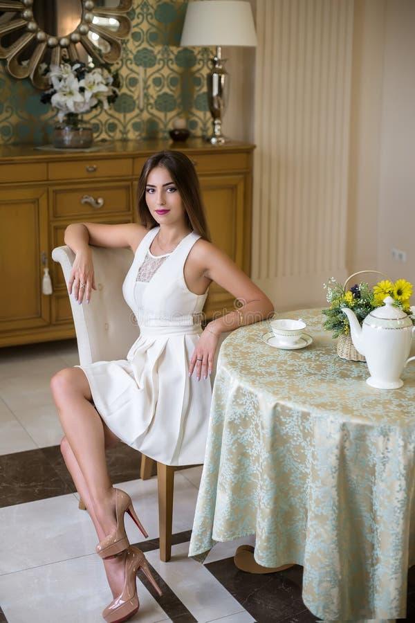 Bella ragazza alla moda che posa in uno studio interno La ragazza sta sedendosi nella camera di albergo Foto di modo immagini stock