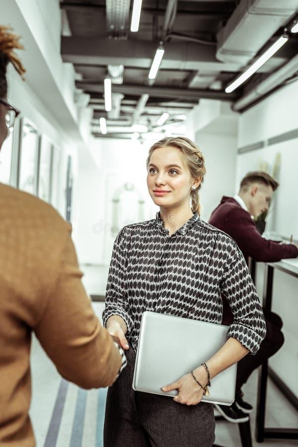Bella ragazza alla moda che tiene il suo computer portatile e che tocca mano del tipo dalla carnagione scura fotografia stock