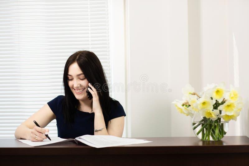 Bella ragazza alla reception che risponde alla chiamata in ufficio dentario immagini stock libere da diritti