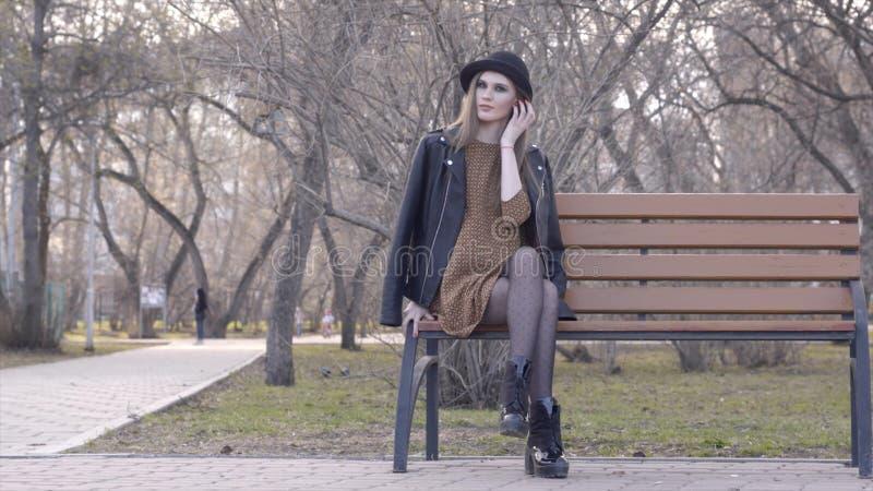 Bella ragazza allegra in cappello che si siede sul banco nel parco soleggiato di autunno azione Bella giovane donna in cappello c fotografia stock libera da diritti