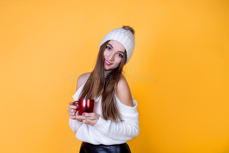 Bella ragazza allegra con una tazza in un maglione su un fondo isolato luminoso di giallo immagine stock