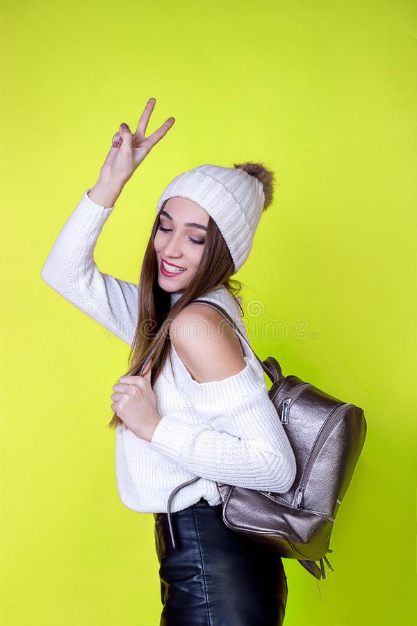 Bella ragazza allegra con uno zaino in un maglione su un fondo isolato luminoso fotografia stock
