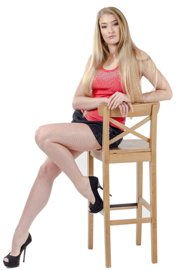 Bella ragazza allegra dai capelli lunghi in una minigonna che si siede su una sedia e su un gesturing immagini stock