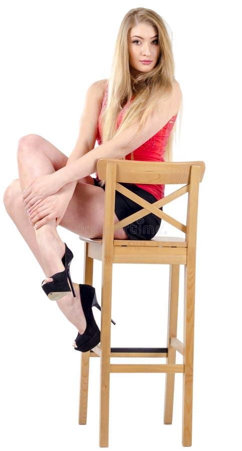 Bella ragazza allegra dai capelli lunghi in una minigonna che si siede su una sedia e su un gesturing immagini stock libere da diritti