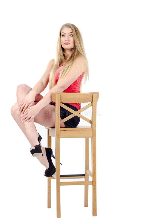 Bella ragazza allegra dai capelli lunghi in una minigonna che si siede su una sedia e su un gesturing fotografia stock