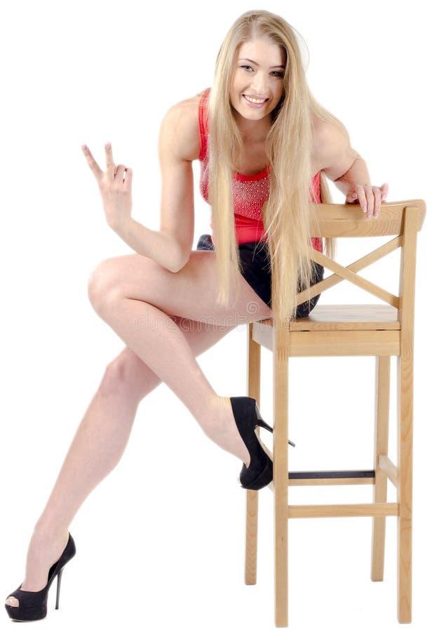 Bella ragazza allegra dai capelli lunghi in una minigonna che si siede su una sedia e su un gesturing fotografie stock libere da diritti