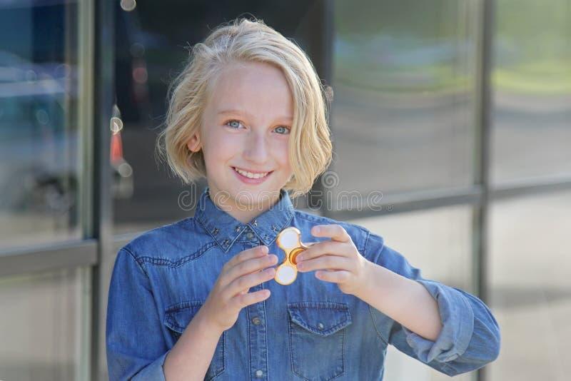 Bella ragazza allegra della scuola che gioca con un filatore di irrequietezza dell'oro Un giocattolo d'avanguardia popolare fotografie stock libere da diritti