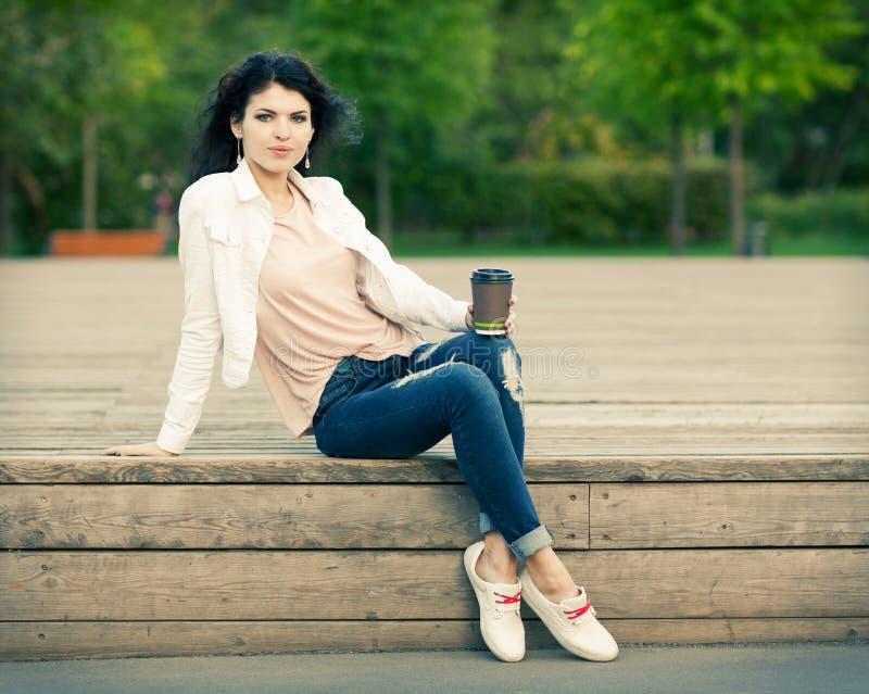 Bella ragazza alta con capelli lunghi castana in jeans che si siedono sulle vecchie plance di legno con una tazza di caffè dispon fotografia stock libera da diritti