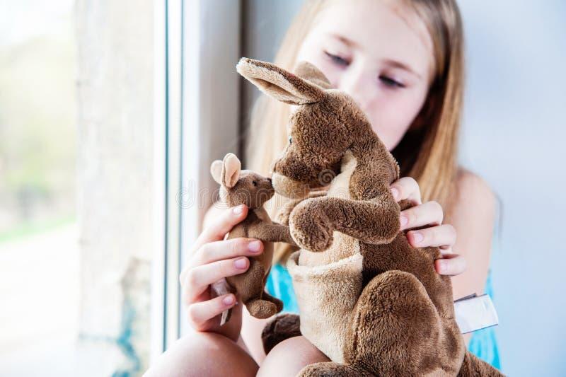 Bella ragazza 8 anni che giocano con i suoi grandi e piccoli canguri del giocattolo fotografie stock libere da diritti